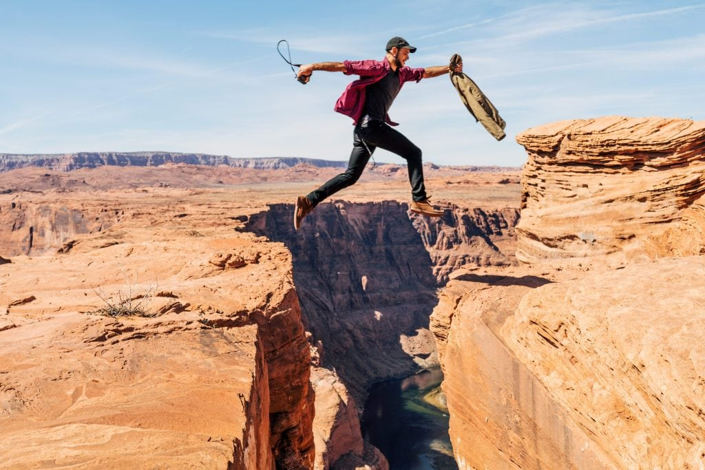 Man in mid-air. leaping across a canyon.