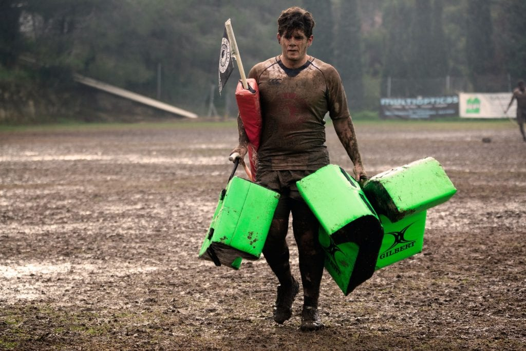 Man covered in mud carrying rugby practice equipment.