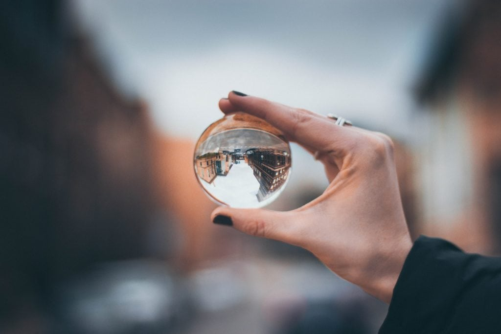 Hand holding a glass sphere which has inverted the the street and buildings.